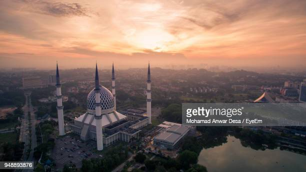 high angle view of city lit up during sunset - shah alam stock photos and pictures