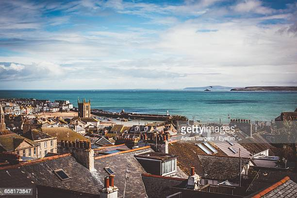 high angle view of city scape against sea and cloudy sky - penzance stock pictures, royalty-free photos & images
