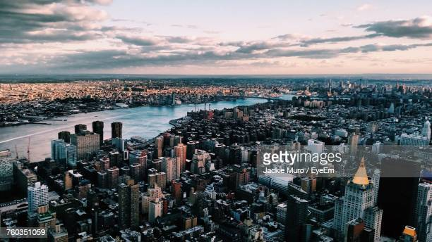 high angle view of cityscape against cloudy sky - muro stock photos and pictures