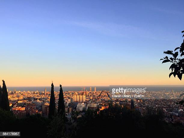 High Angle View Of Cityscape And Sea Against Blue Sky At Sunset
