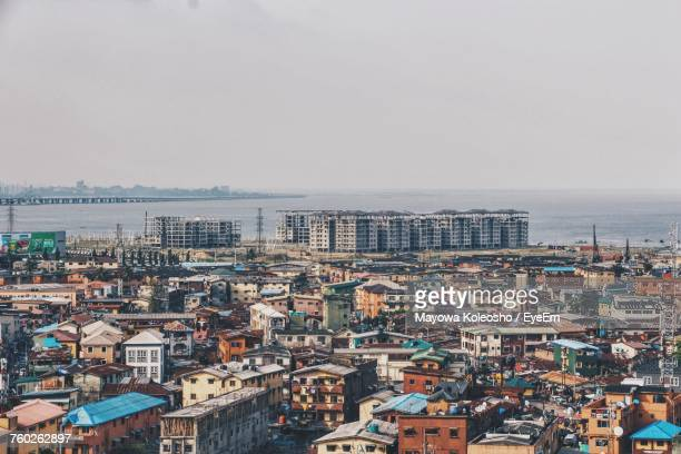 high angle view of cityscape by sea against clear sky - lagos nigeria stock pictures, royalty-free photos & images