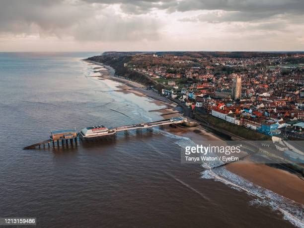 high angle view of cityscape by sea against sky - norfolk east anglia foto e immagini stock