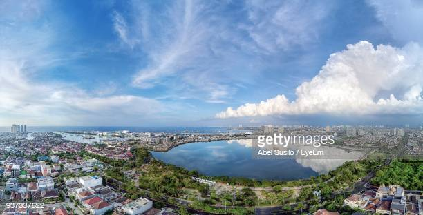high angle view of cityscape by sea against sky - jakarta foto e immagini stock