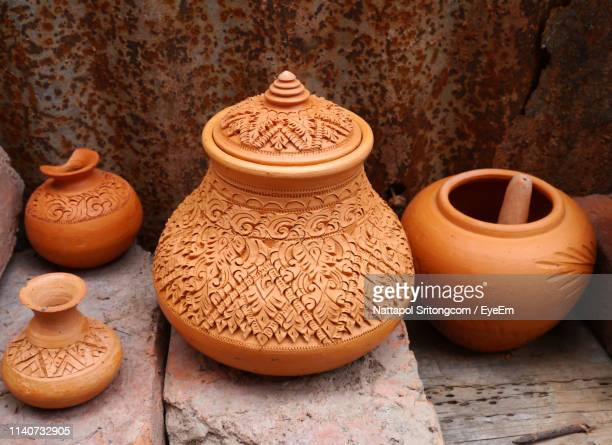 high angle view of clay urns against rusty wall - vaso de barro imagens e fotografias de stock