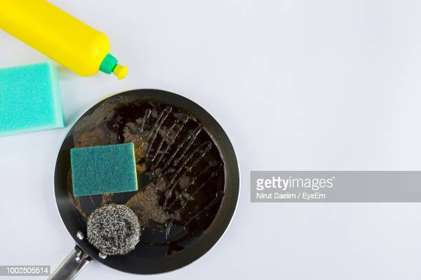 High Angle View Of Cleaning Sponge In Cooking Pan Over White Background