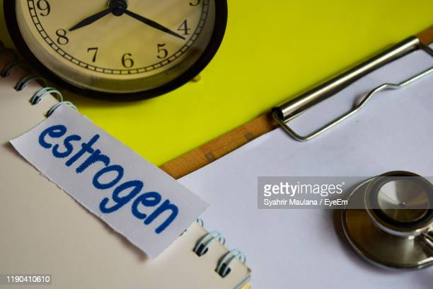 high angle view of clock by clipboard against yellow background - oestrogen stock pictures, royalty-free photos & images