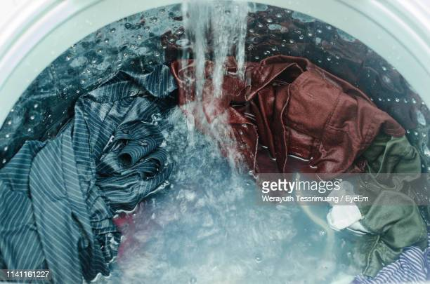 high angle view of clothes being washed in washing machine - waschen stock-fotos und bilder