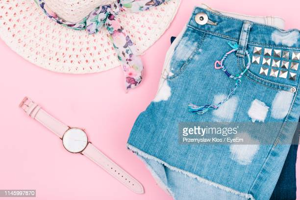 high angle view of clothing and wristwatch against pink background - denim shorts stock pictures, royalty-free photos & images