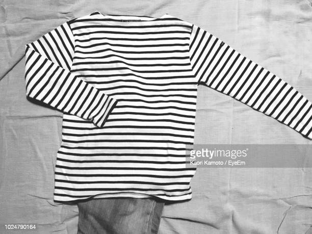 high angle view of clothing on bed - top garment stock pictures, royalty-free photos & images