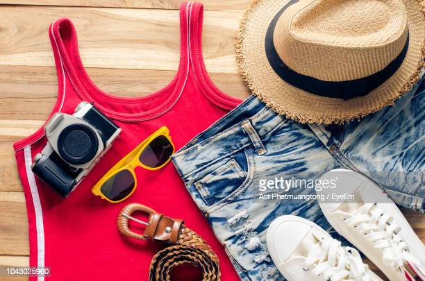 high angle view of clothing with various objects at table - straw hat stock pictures, royalty-free photos & images