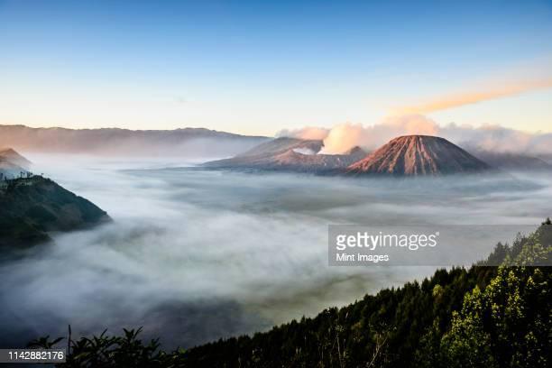 high angle view of clouds under smoking volcano - erupting stock-fotos und bilder