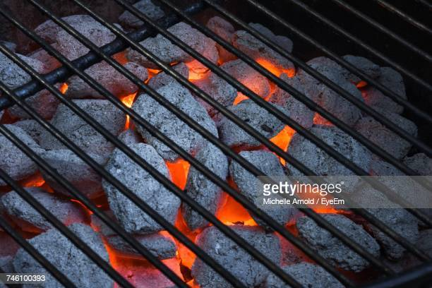 high angle view of coals burning in barbecue grill - metal grate stock photos and pictures