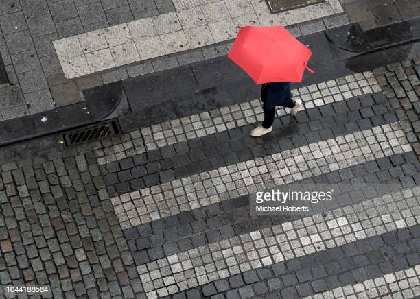 high angle view of cobbled street and person walking with umbrella - umbrella stock pictures, royalty-free photos & images