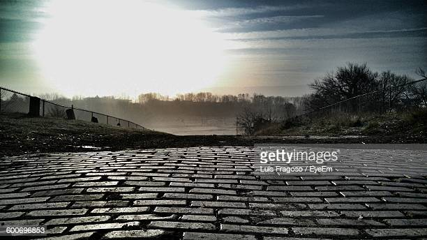High Angle View Of Cobblestone Street Against Cloudy Sky
