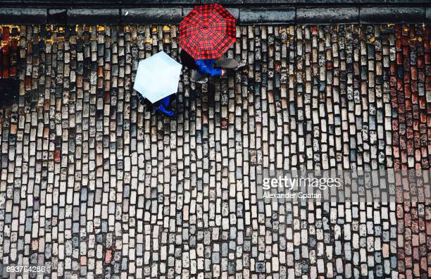High angle view of cobblestone street and umbrellas