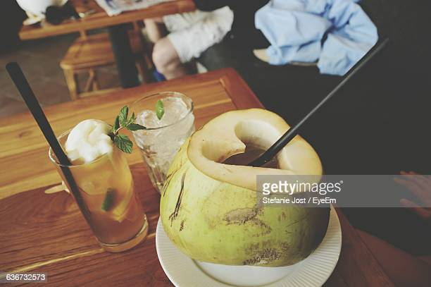 high angle view of coconut water on table - coconut water stock pictures, royalty-free photos & images