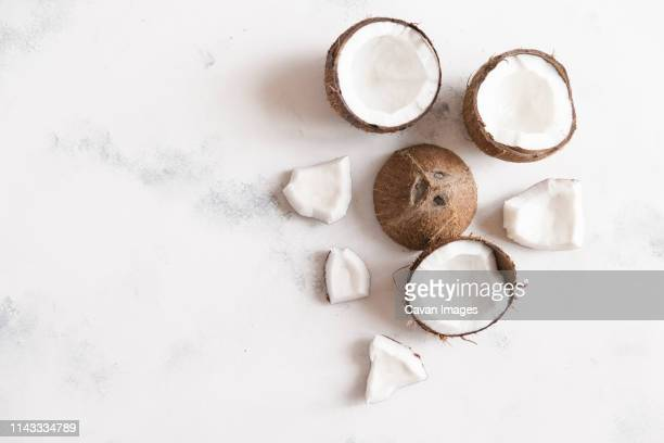 high angle view of coconuts on white table - coconut stock pictures, royalty-free photos & images