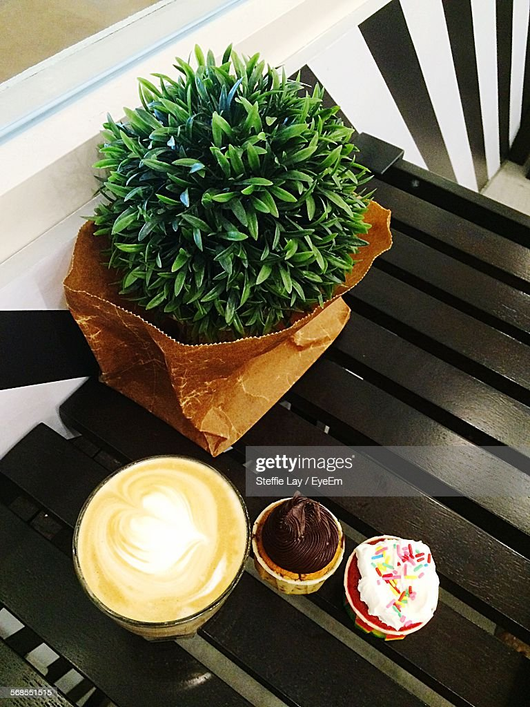 High Angle View Of Coffee And Cup Cakes By Plant In Paper Bag On Table Indoors : Stock Photo