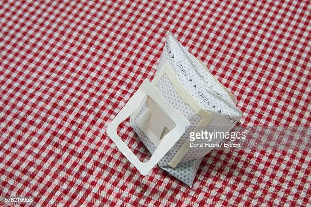 High Angle View Of Coffee Bag On Tablecloth