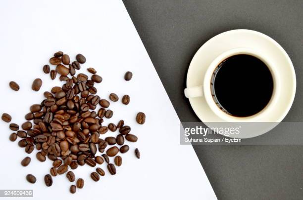 high angle view of coffee beans by coffee on table - coffee beans stock photos and pictures