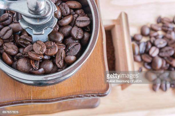 high angle view of coffee beans on table - coffee grinder stock photos and pictures