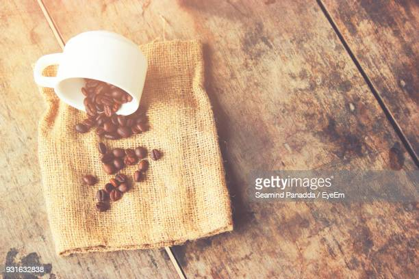 High Angle View Of Coffee Cup And Beans On Jute Over Table