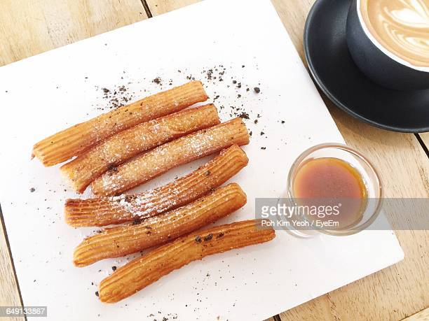 high angle view of coffee cup and churros with salted caramel on table - churro stock photos and pictures