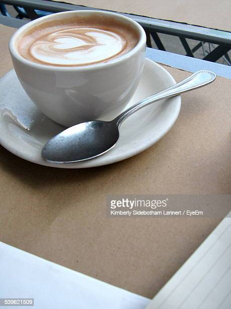 High Angle View Of Coffee Cup And Saucer With Spoon In Restaurant Table