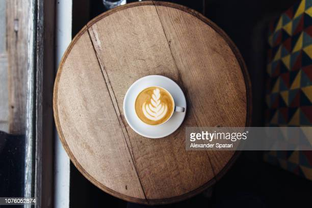 High angle view of coffee cup with latte froth art on round wooden table in cafe