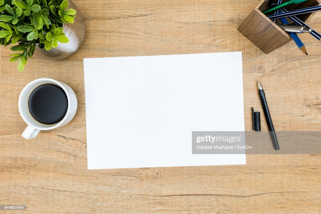 High Angle View Of Coffee Cup With Paper And Potted Plant On Table : Stock Photo