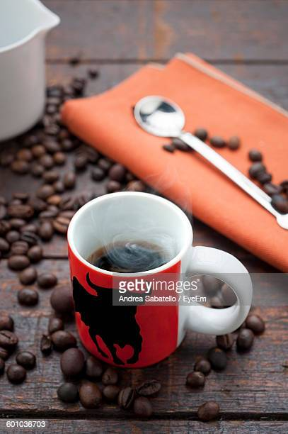 High Angle View Of Coffee Cup With Roasted Coffee Beans On Table
