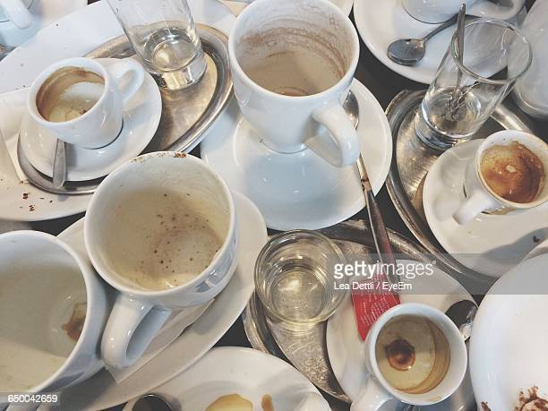 high angle view of coffee cups leftovers on table - glas serviesgoed stockfoto's en -beelden