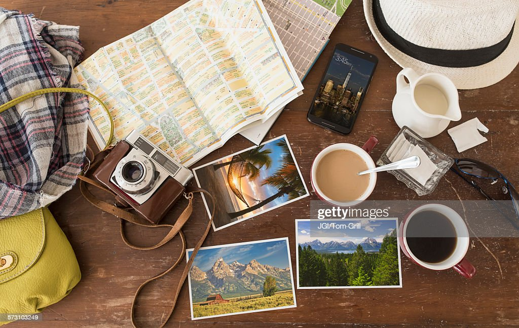 High angle view of coffee, maps, photographs, camera and cell phone : Stock Photo