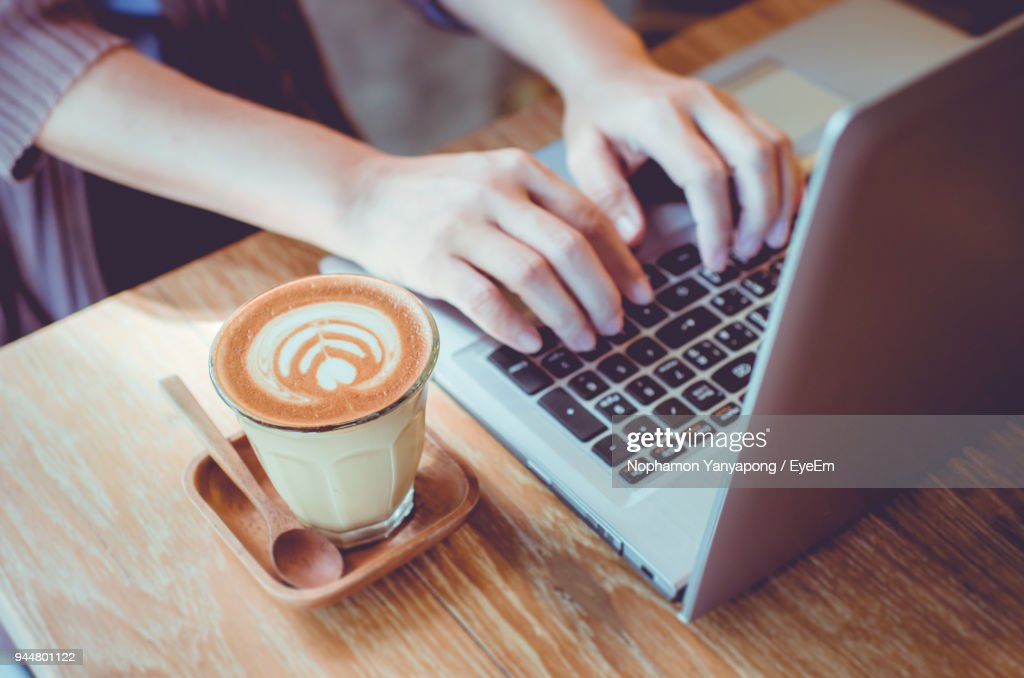 High Angle View Of Coffee Up By Woman Using Laptop : Stock Photo