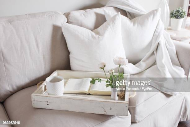 high angle view of coffee with book and flower vase on sofa at home - bedding stock pictures, royalty-free photos & images