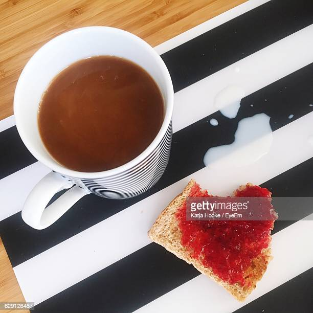 High Angle View Of Coffee With Bread And Jam On Striped Tray