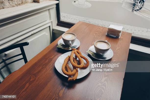 high angle view of coffee with churros served on wooden table - churro fotografías e imágenes de stock