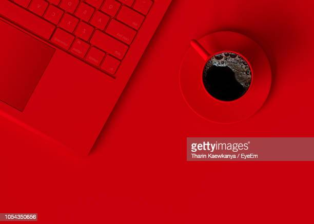 high angle view of coffee with laptop on red background - isolated color stock pictures, royalty-free photos & images