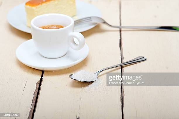 High Angle View Of Coffee With Sugar And Cheesecake On Table