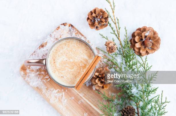 High Angle View Of Coffee With Twigs And Pine Cones Amidst Fake Snow