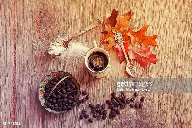 High Angle View Of Coffee With Vintage Spoons And Autumn Leaves On Table