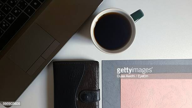 High Angle View Of Coffee With Wallet And Laptop On Table