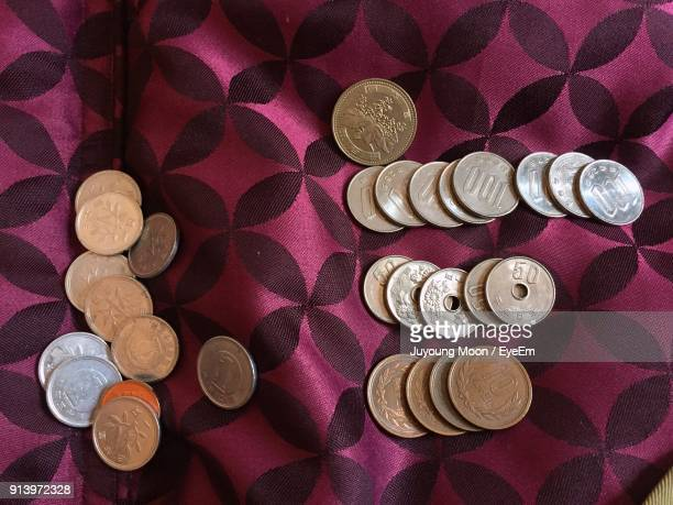 High Angle View Of Coins On Bed