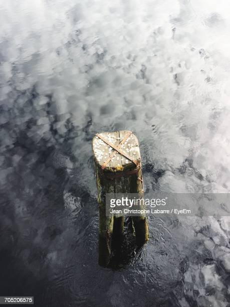 High Angle View Of Coins On Wooden Post In Rippled Lake With Reflection Of Clouds