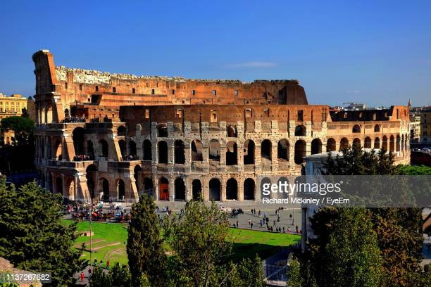 high angle view of coliseum against blue sky during sunny day - coliseum rome stock photos and pictures