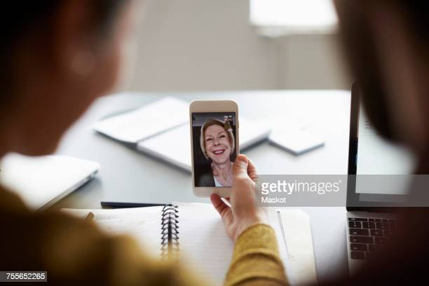 high angle view of colleagues video conferencing with senior businesswoman on smart phone in board room - working seniors stock pictures, royalty-free photos & images