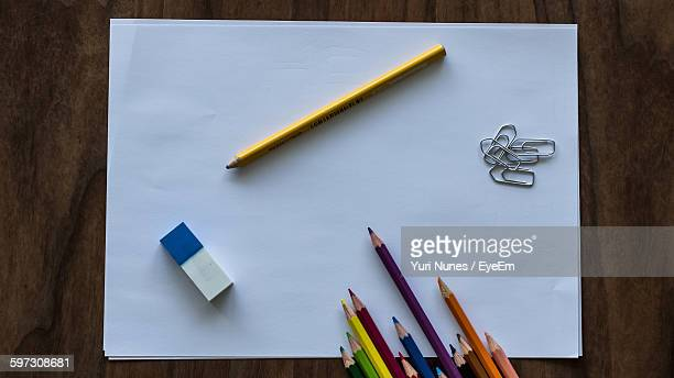 High Angle View Of Colored Pencils With Eraser And Paper Clips On Paper