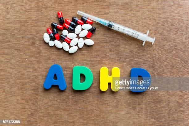 High Angle View Of Colorful Adhd Text With Syringe And Pills On Wooden Table