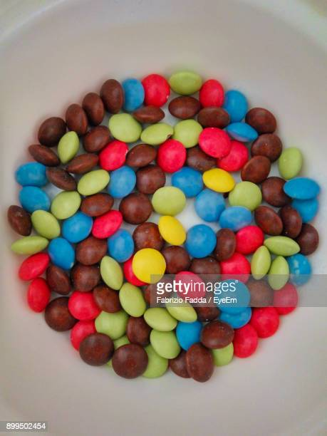 high angle view of colorful candies in bowl - bowl of candy stock photos and pictures