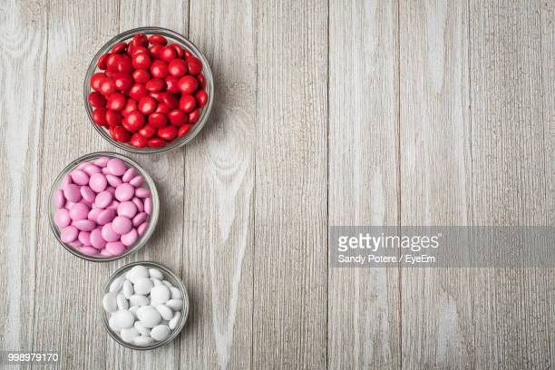 High Angle View Of Colorful Candies In Bowls On Wooden Table